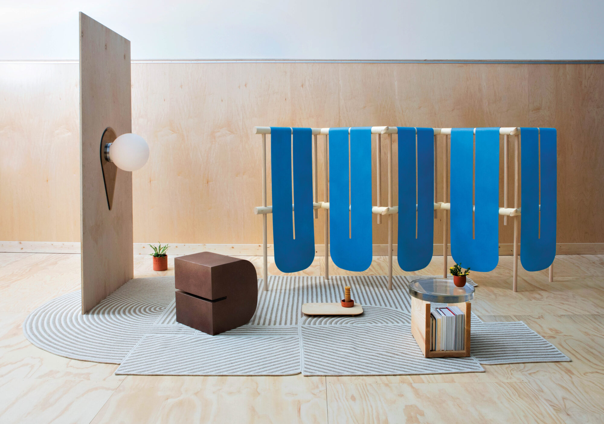 Hanging blue panels behind furnishings and striped rug