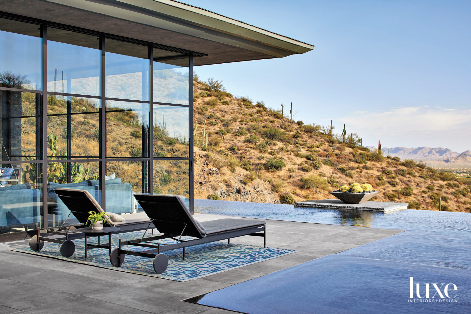 Two lounge chairs on the patio overlook an infinity pool and the mountains beyond.