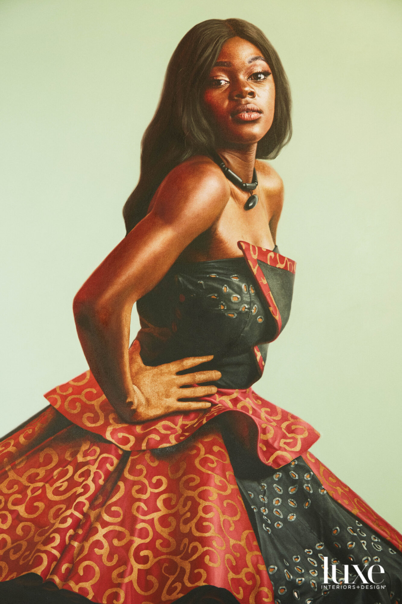 A Black woman with long hair in a black-and-red strapless dress