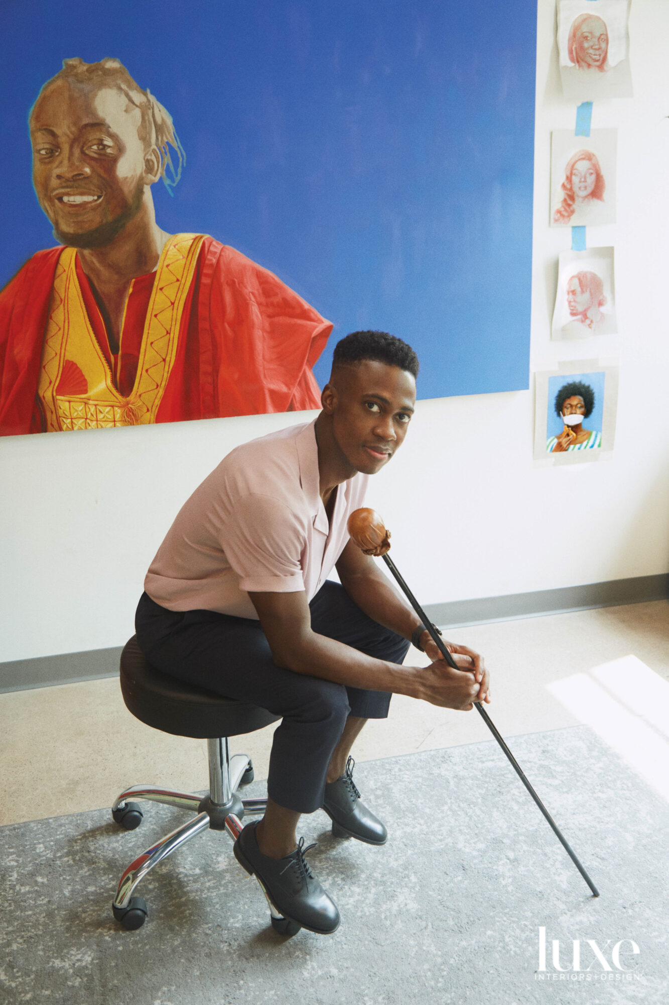 Artist Papay Solomon in front of a portrait.