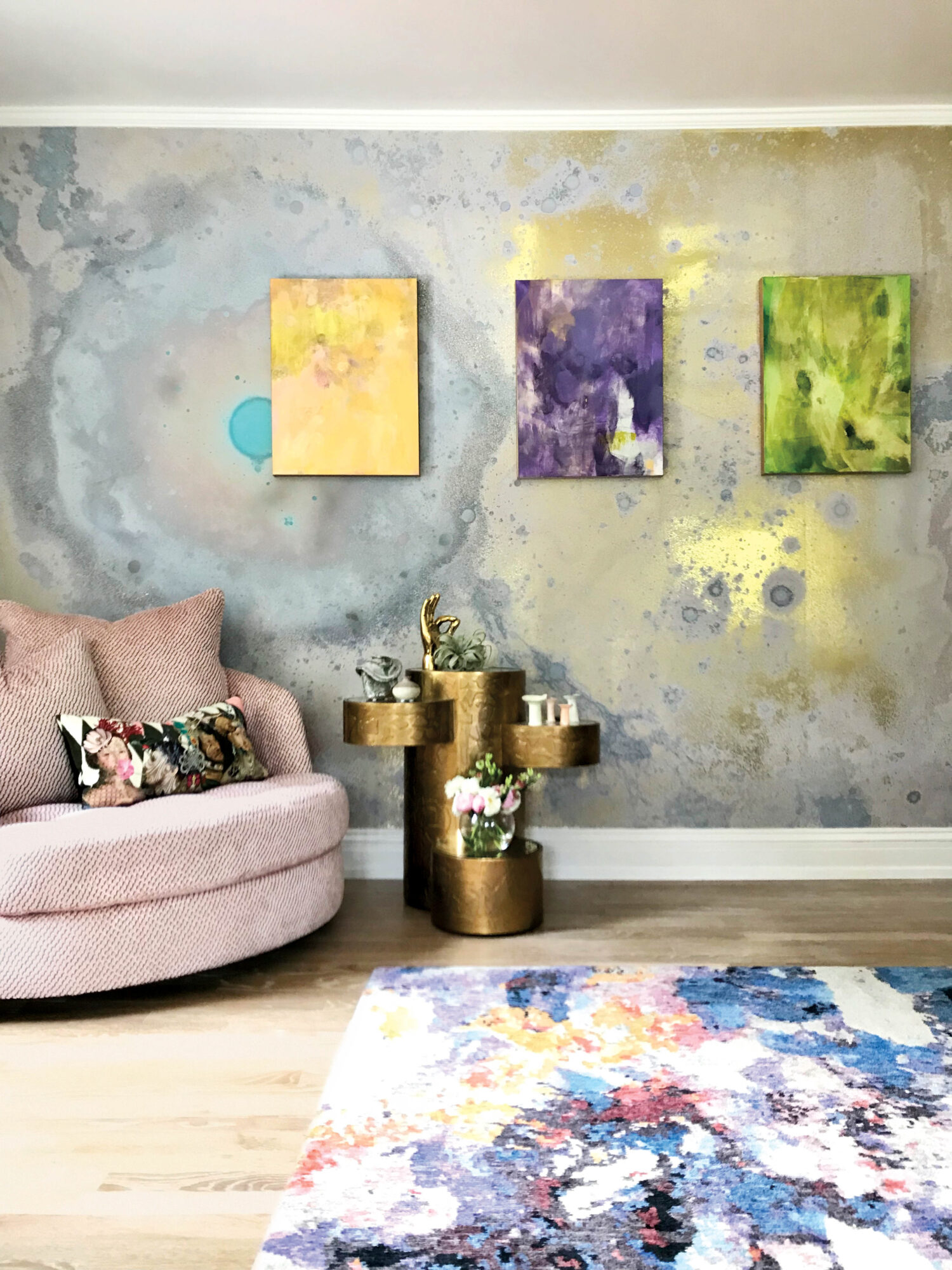 vignette of pink chair, colorful rug and yellow, purple and green artworks