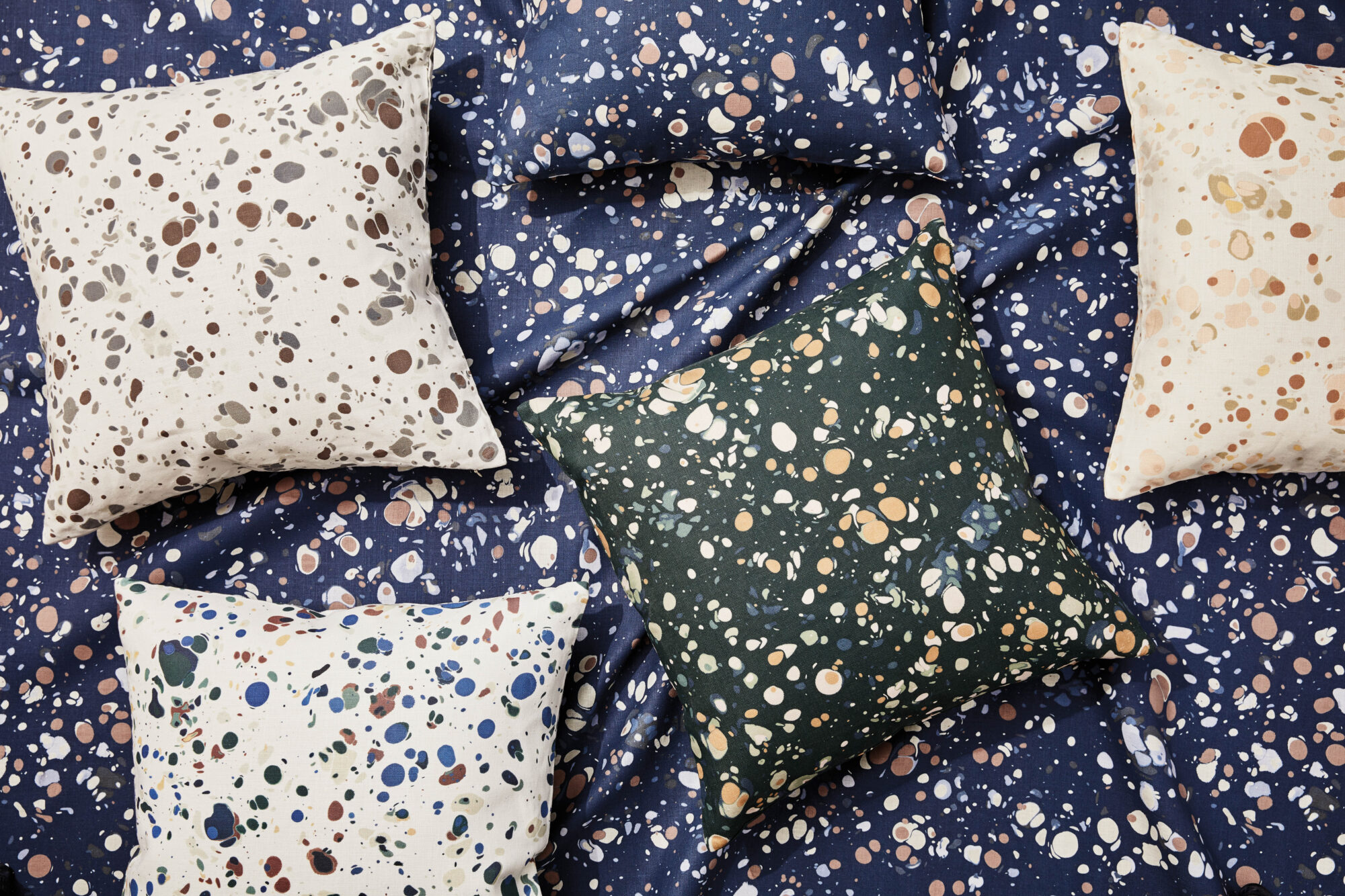 shot of painterly pillows and fabric