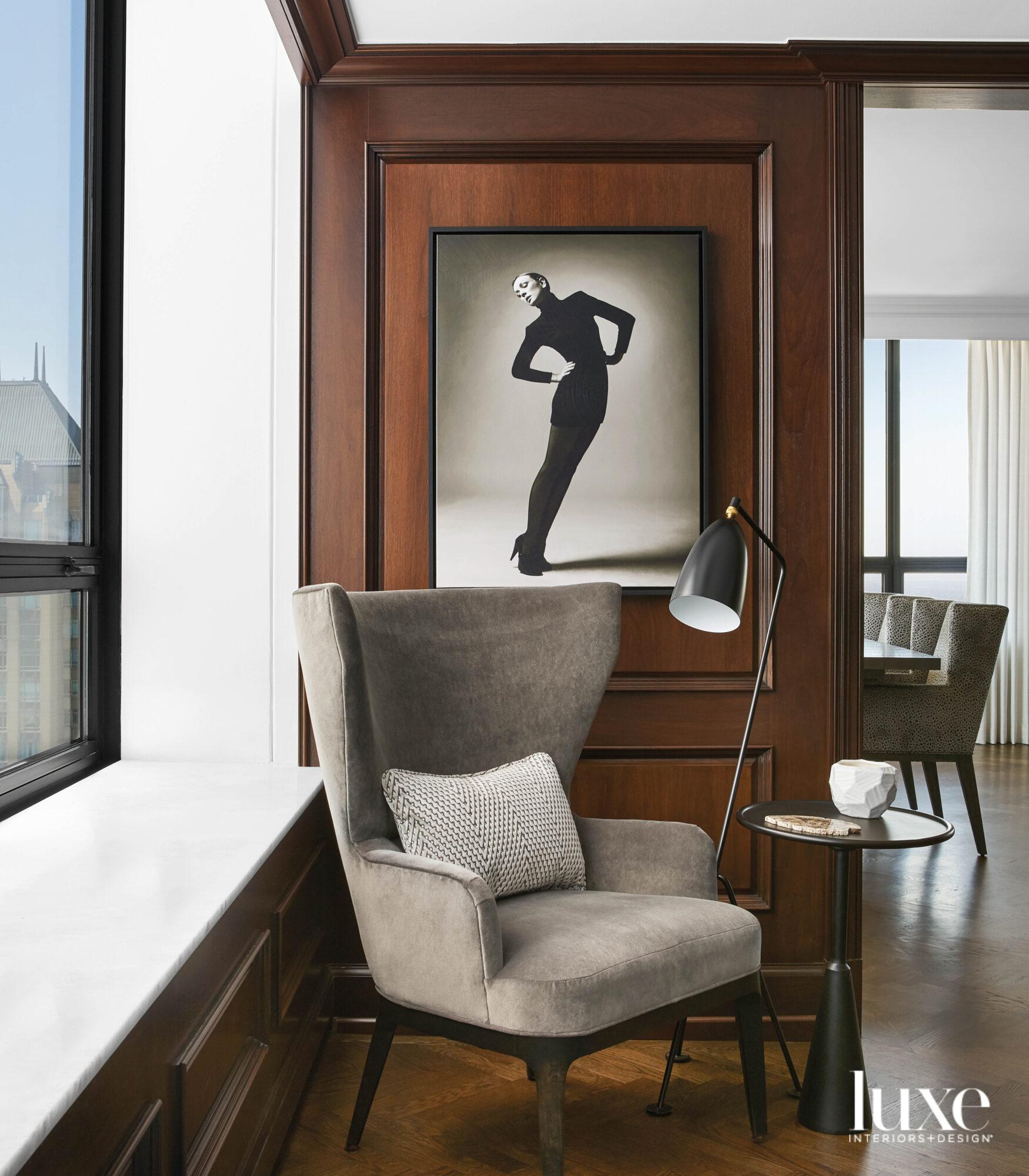 A gray velvet chair sits...