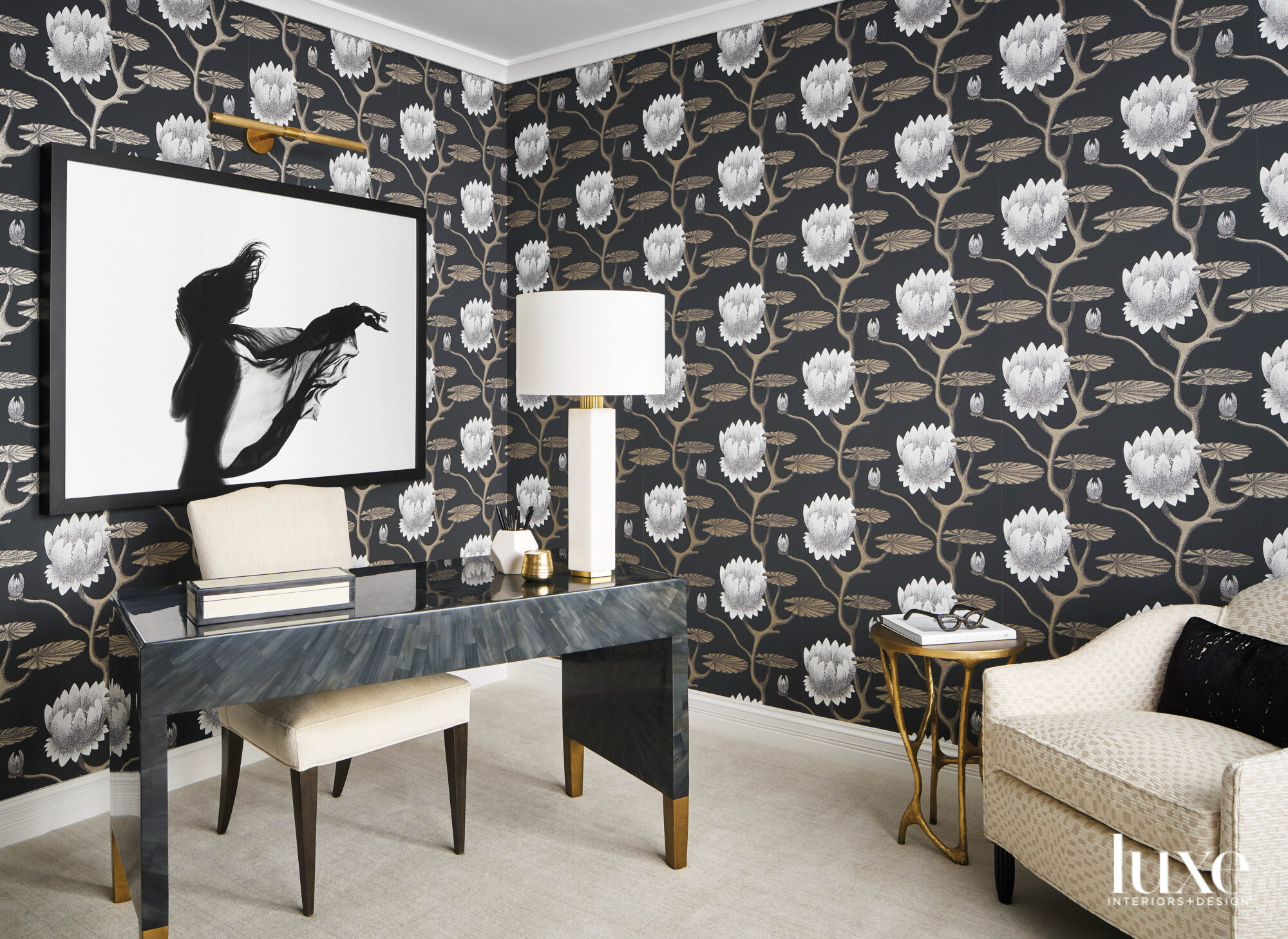A home office has a dramatic floral wallpaper. A black-and-white photograph hangs behind the desk.