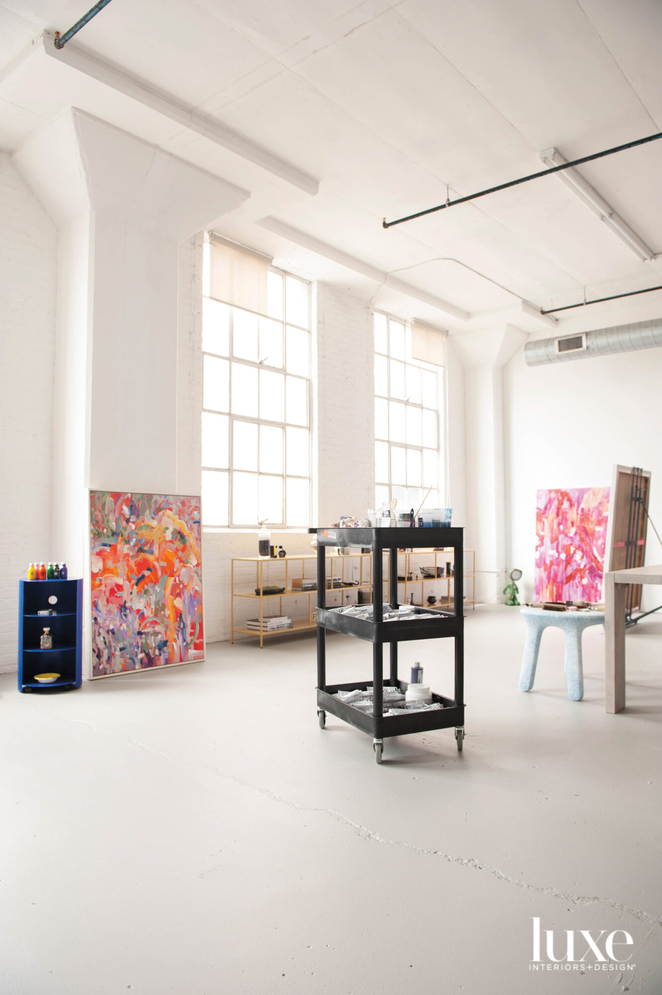 A large white studio with large windows and two colorful abstract paintings.