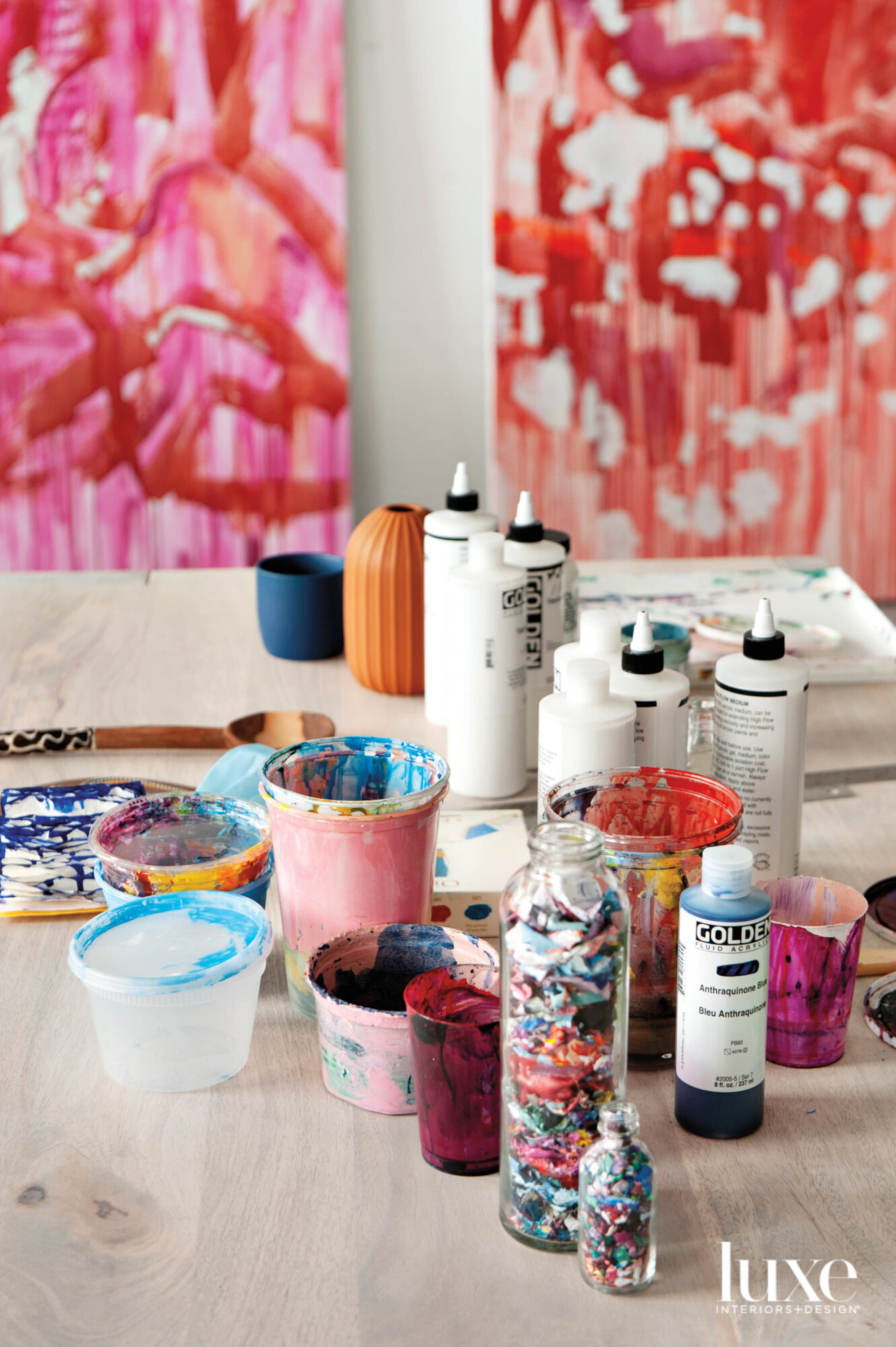 Paint and materials are in the forefront on the table and two abstract paintings hang behind it.