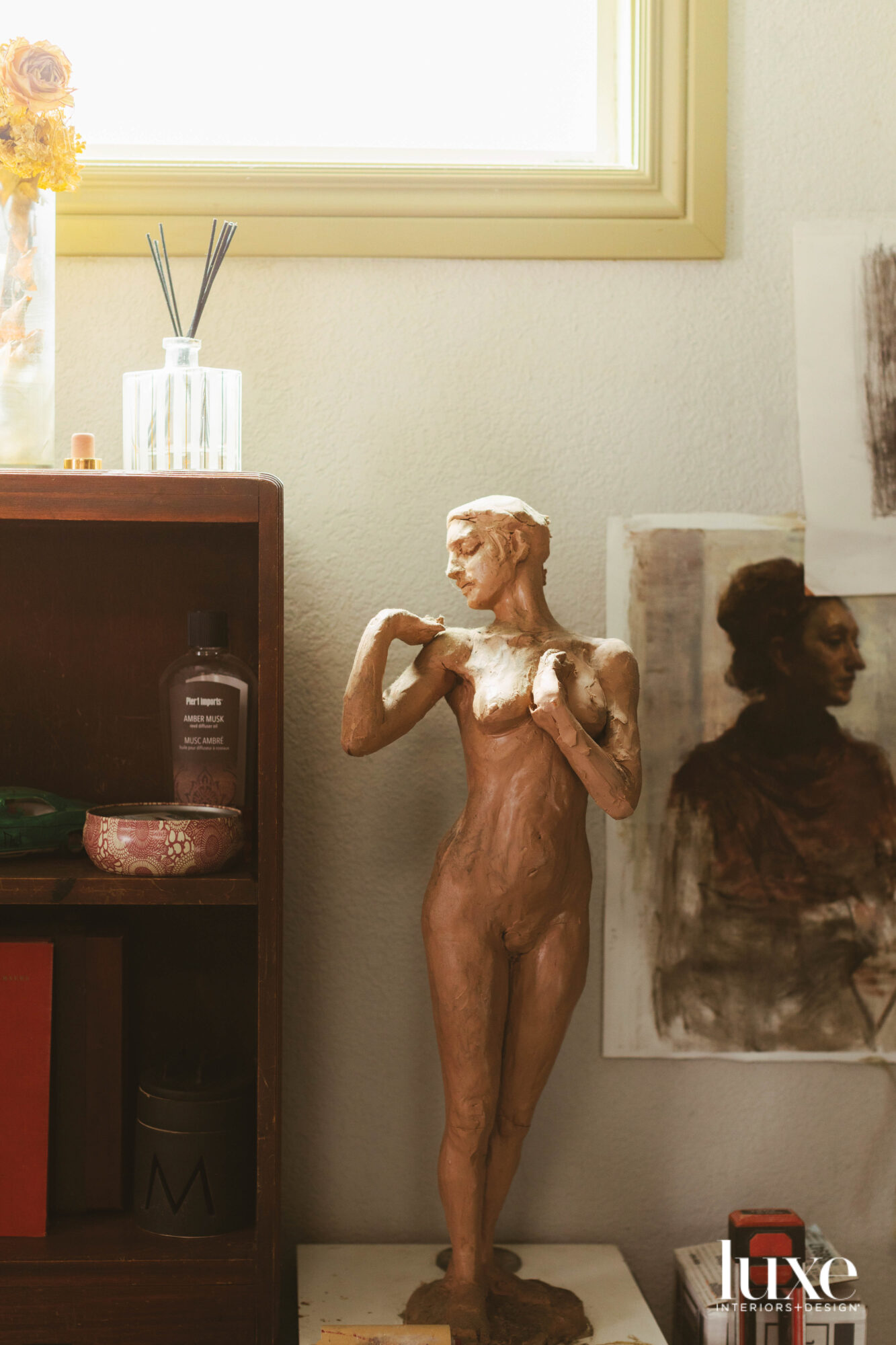 A terracotta-hued sculputure of a woman's form is found in an artist's studio