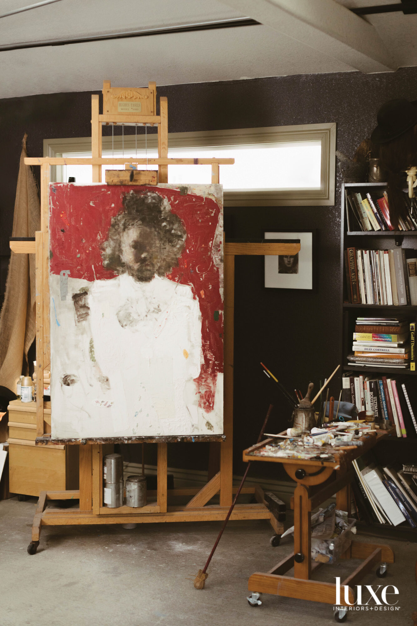 easel with painting of a young girl in white dress