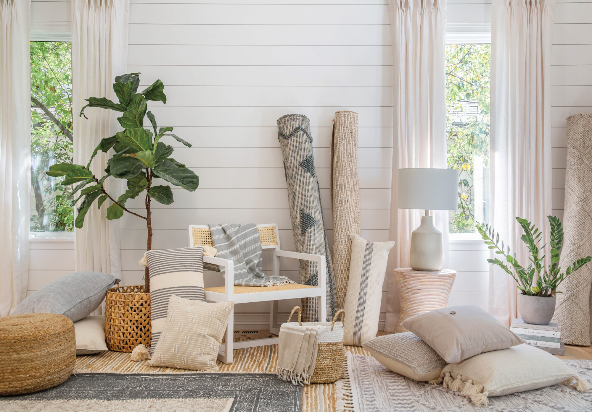 stacks of pillows and fabric with plants in the corners