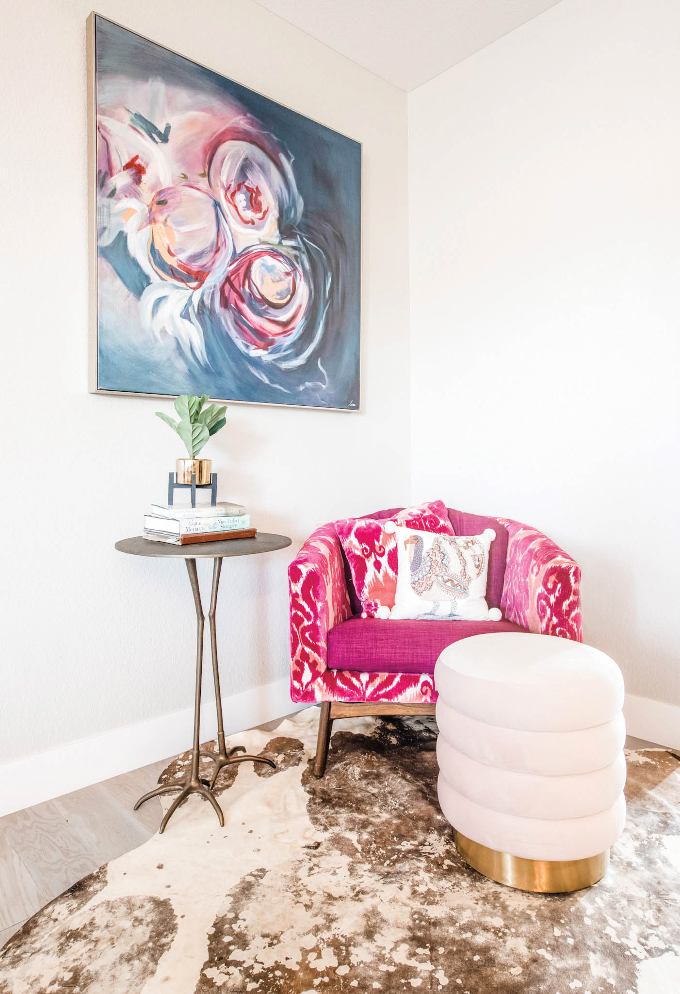 vignette of pink floral chair and floral painting