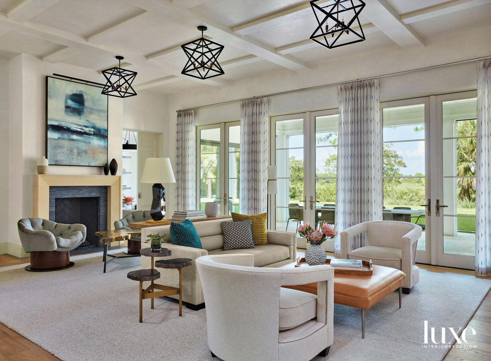 living area with three iron chandeliers, fireplace and two seating areas