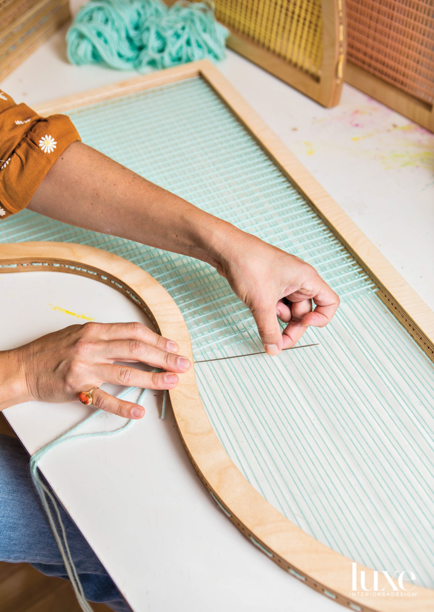 artist Hayley Sheldon threads mint-colored yarn into a screen