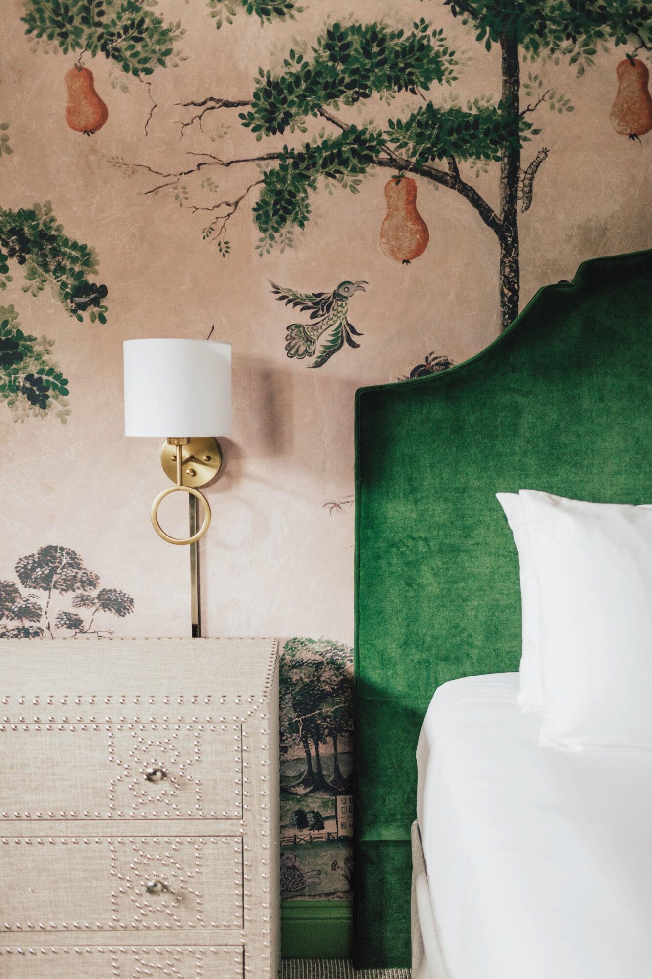 green headboard against botanical wallpaper