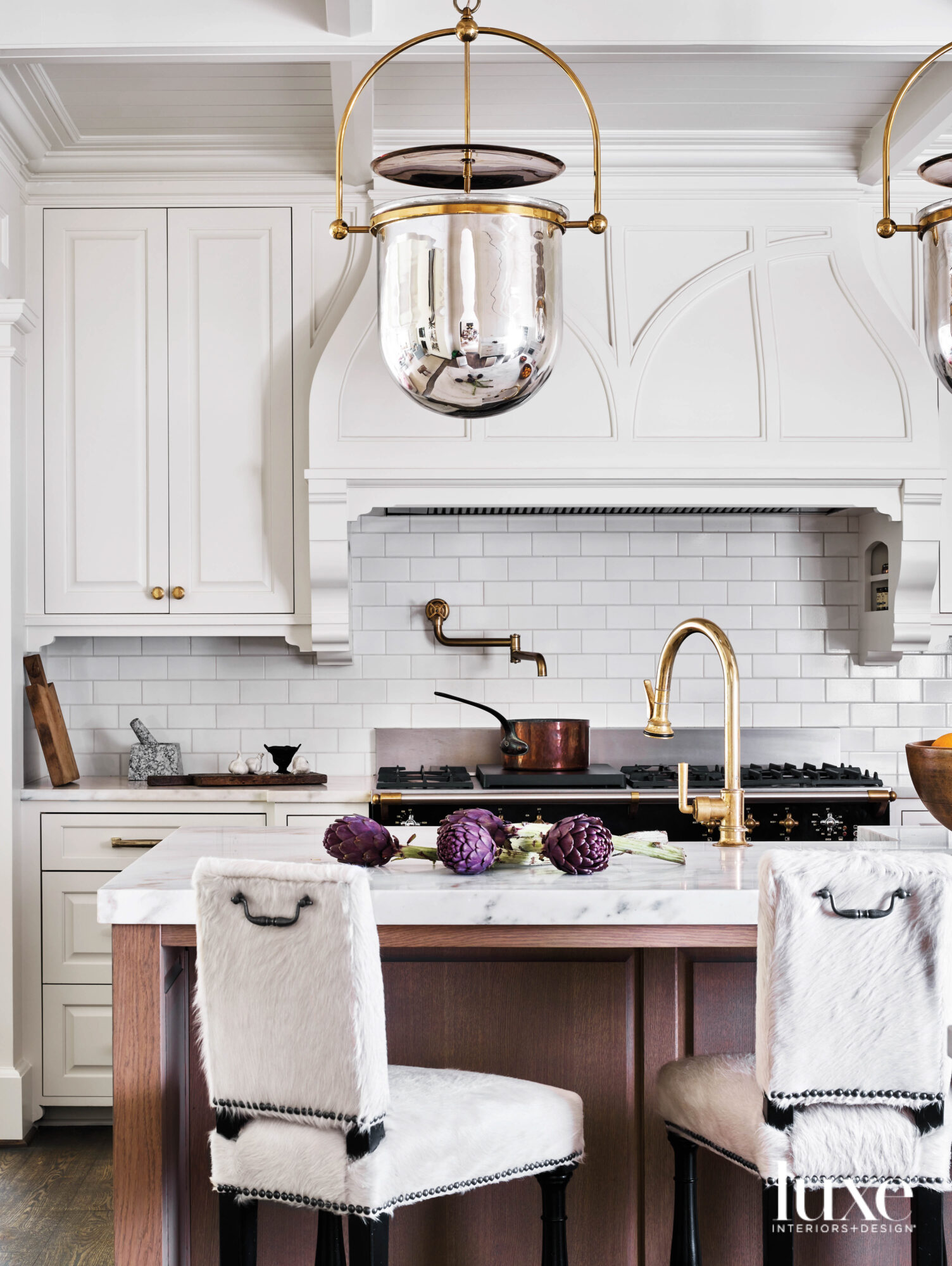 Classic kitchen with white subway tile backsplash, mohair-covered counter stools and mercury glass bell jar ceiling pendants