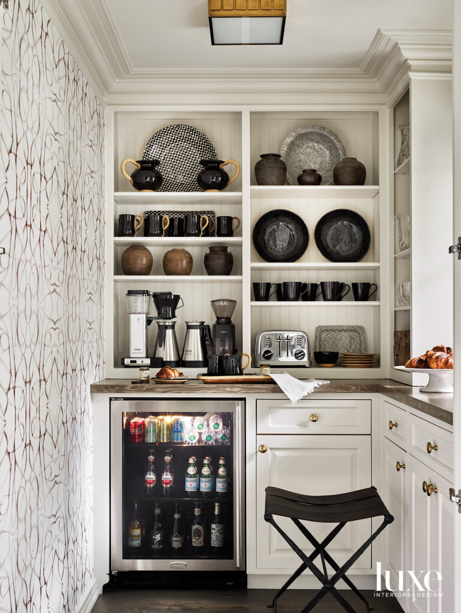 Well-appointed pantry with patterened wallpaper, built-in display shelves and creamy paint color