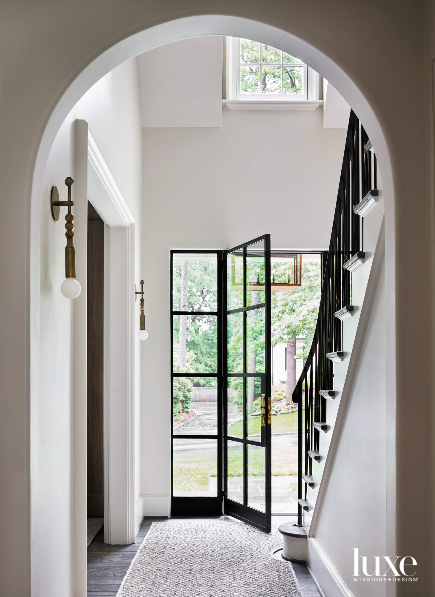 Bright entryway with iron-and-glass front...