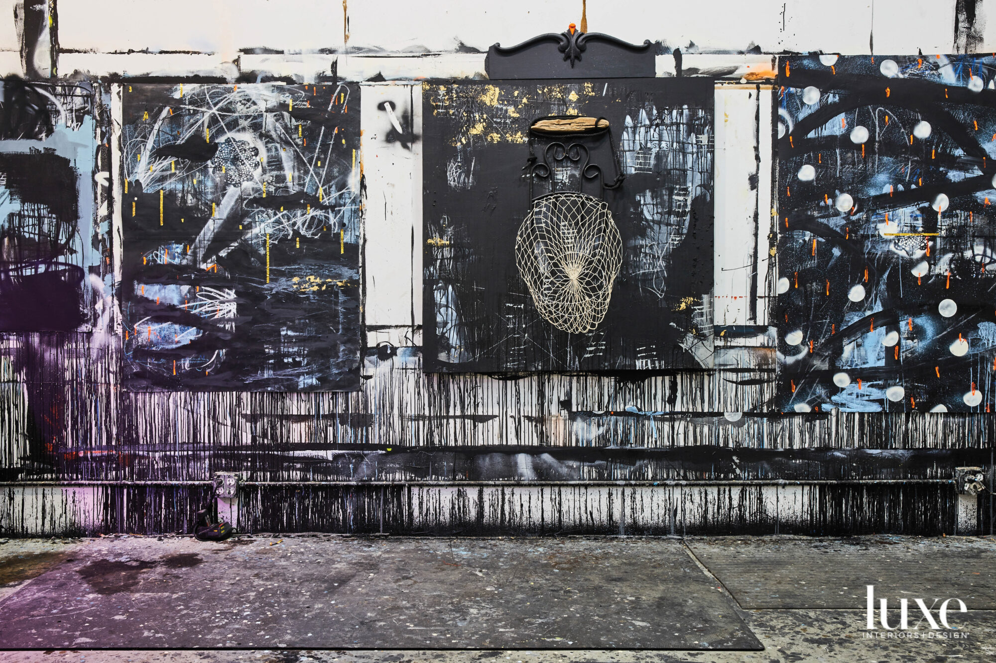 Interior of a room with paint-splattered concrete floors and three dark abstract paintings mounted along paint-splattered wall