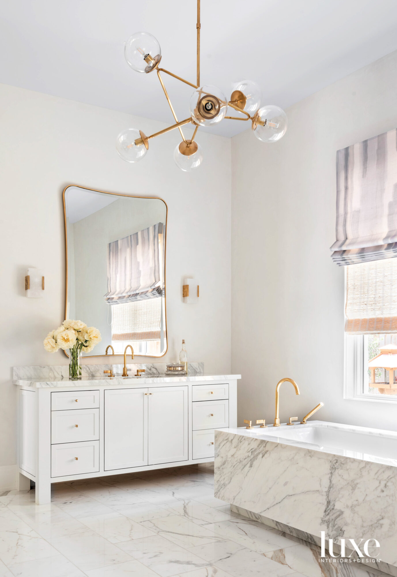 Marble-clad main bathroom with gold...
