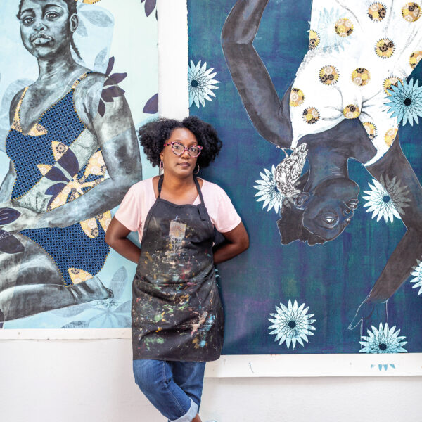 Artist Delita Martin posing in front of her mixed-media prints.