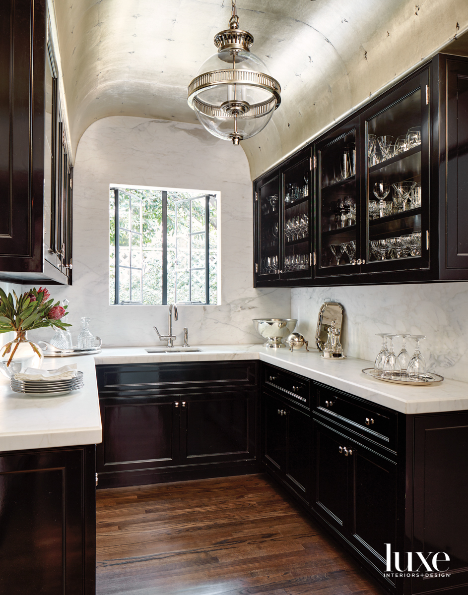 Pantry with black-painted cabinetry and...