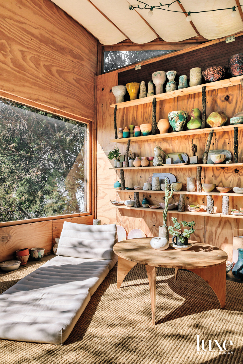 Lee's studio with a low daybed, small table and display of ceramic pieces