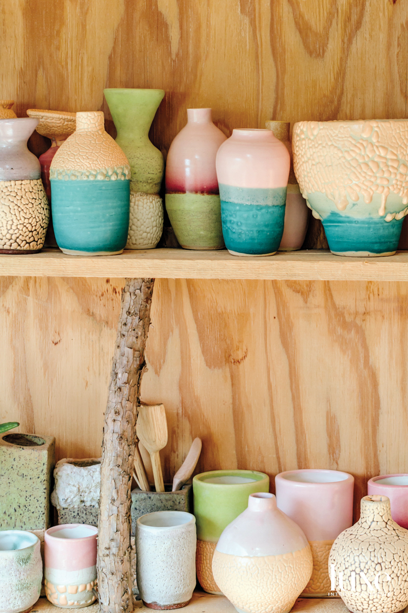 A selection of colorful ceramic vessels on shelves