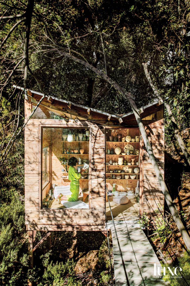 Raina J Lee kneels in her treehouse showroom with shelves of ceramics behind her