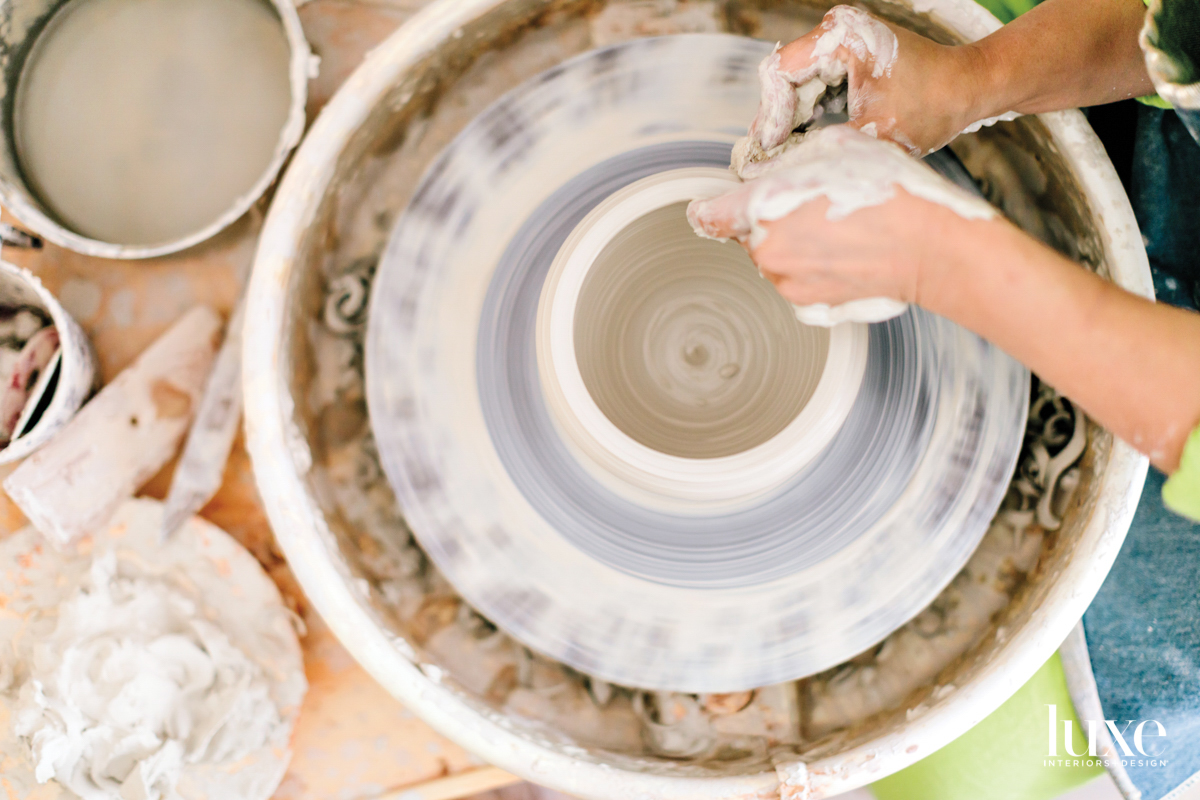 Hands work on bowl on a pottery wheel