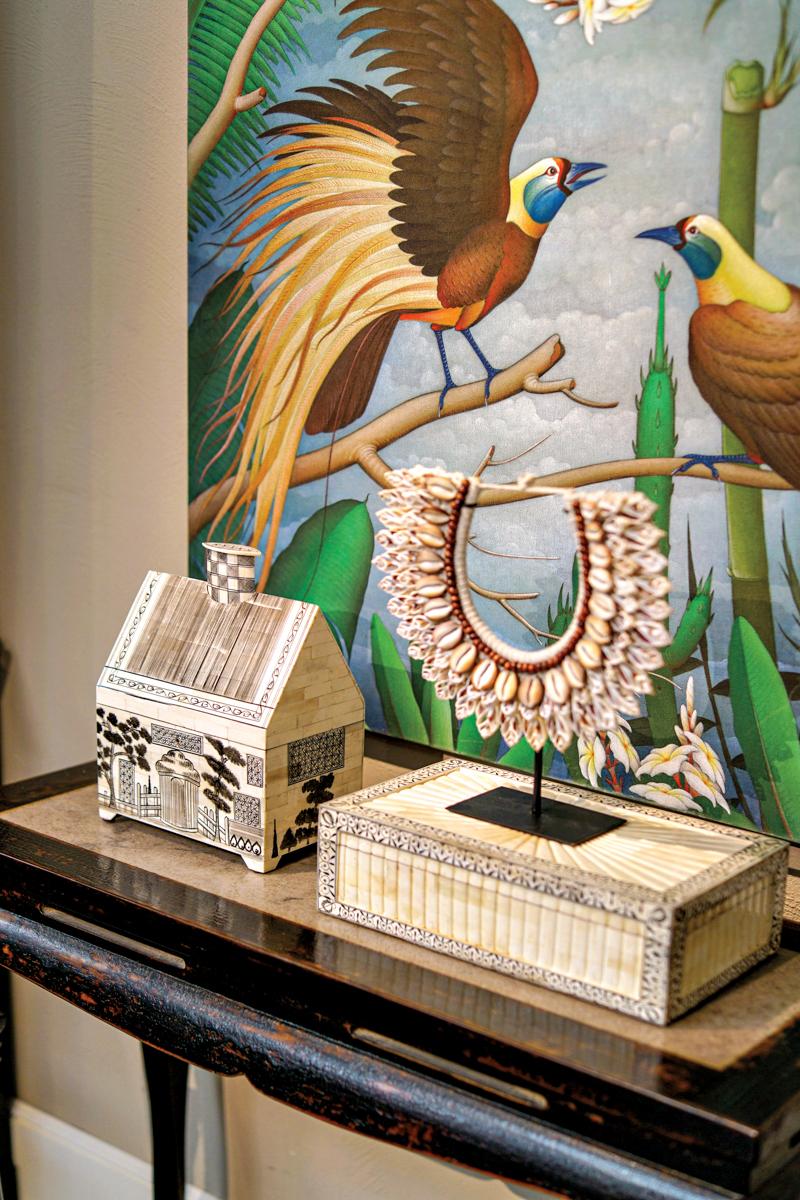 bird artwork behind a shell necklace