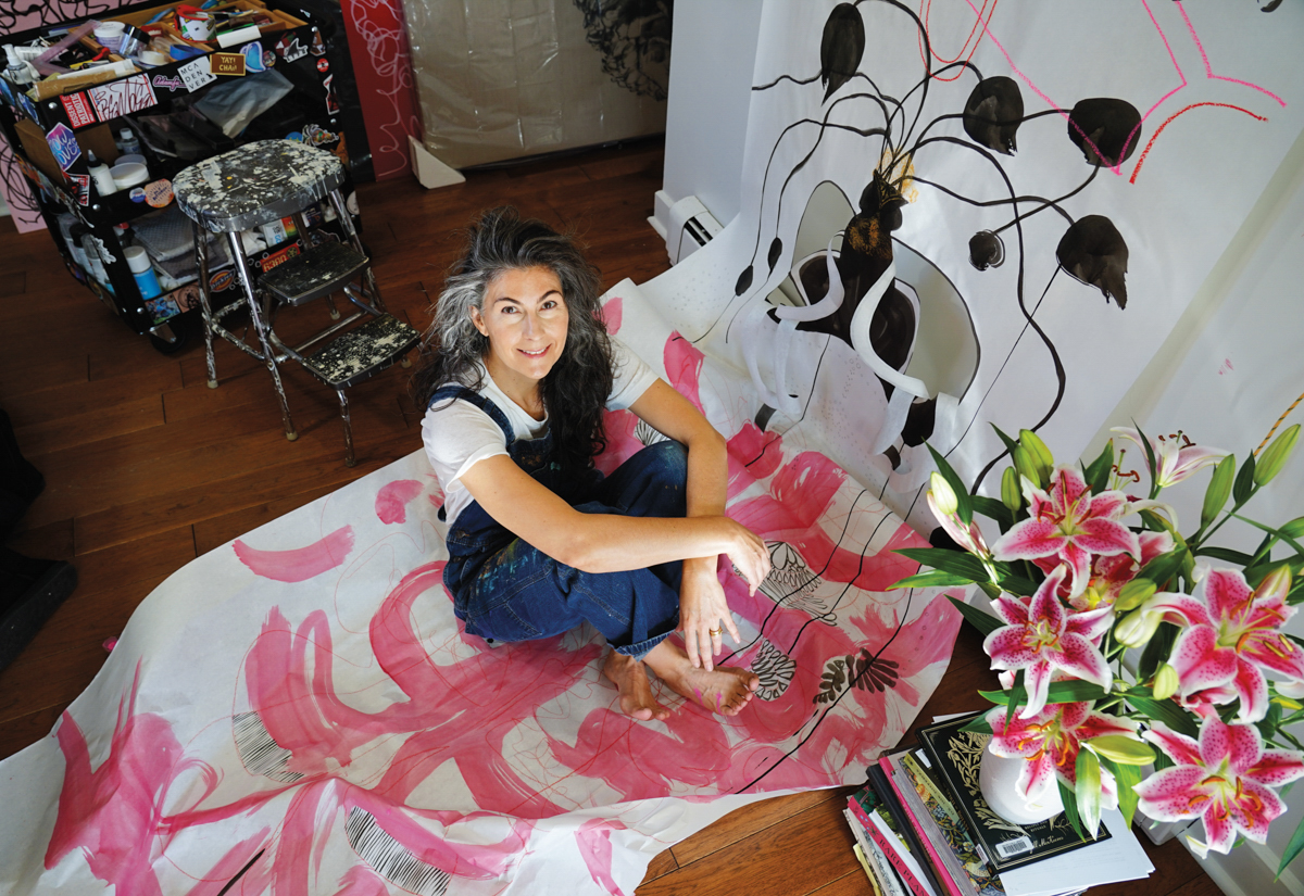 artist sitting among her artwork looking up