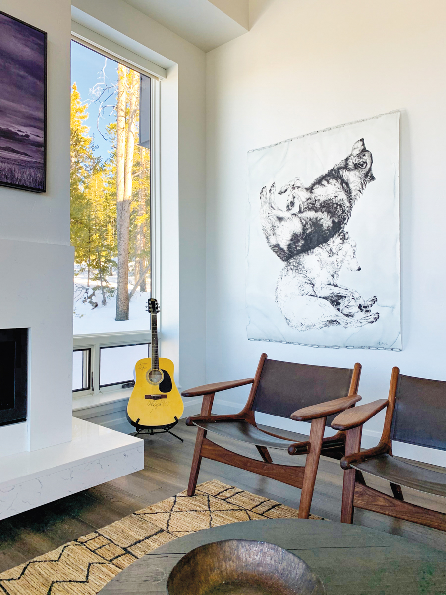 two chairs and a guitar under artwork