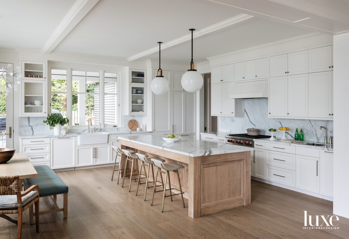 white kitchen with wood island...