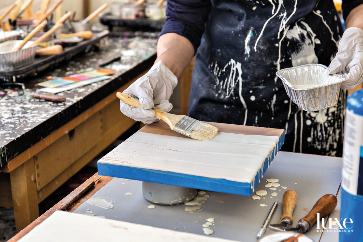 Bowman spreads encaustic paint on to a panel