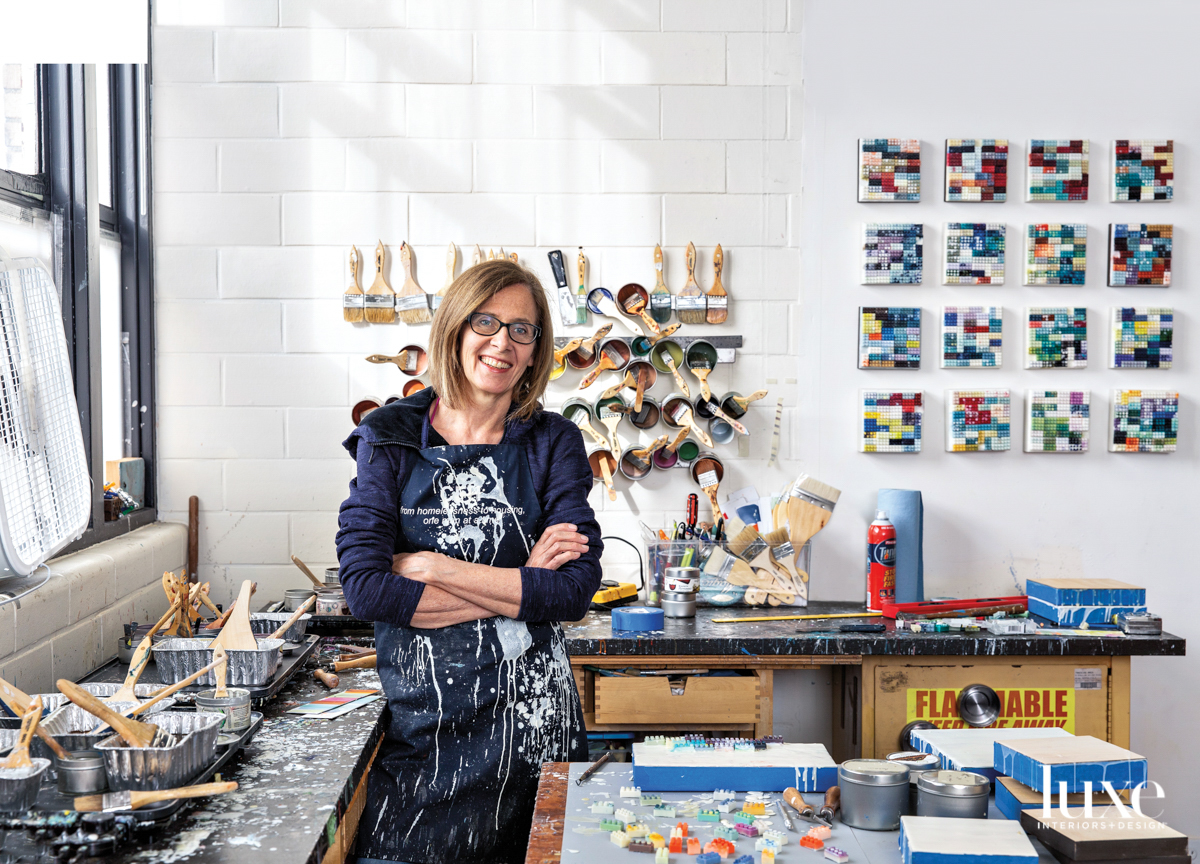 Patti Bowman stands in her studio in front of her encaustic LEGO paintings