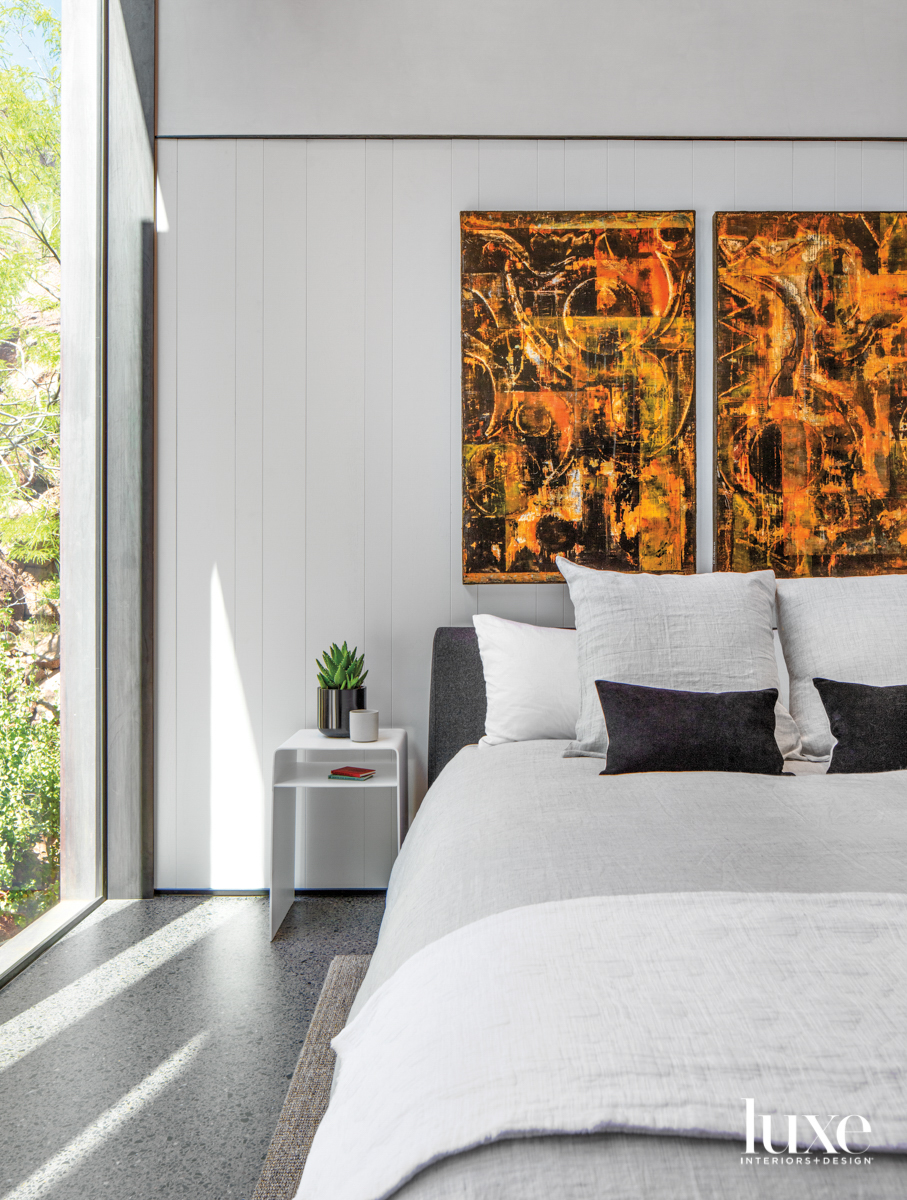 A bedroom with orange abstract...