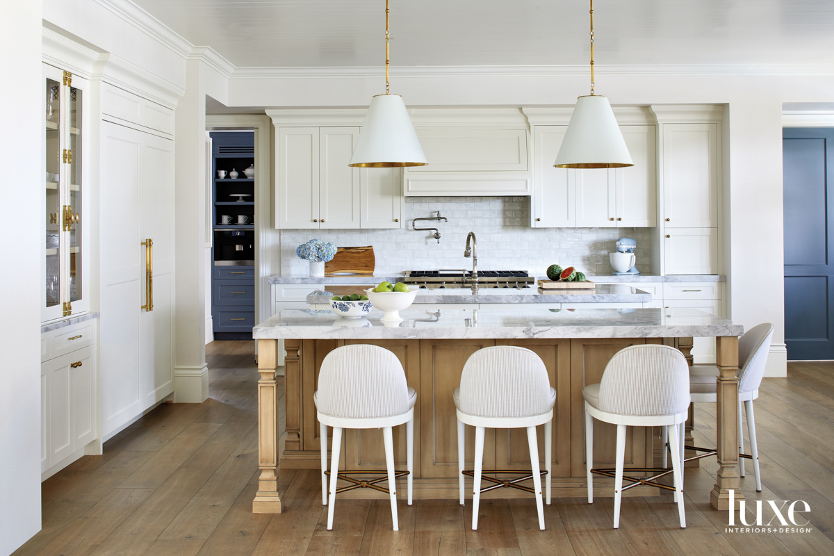 Counter stools lined up at a light wood island with a quartz top.