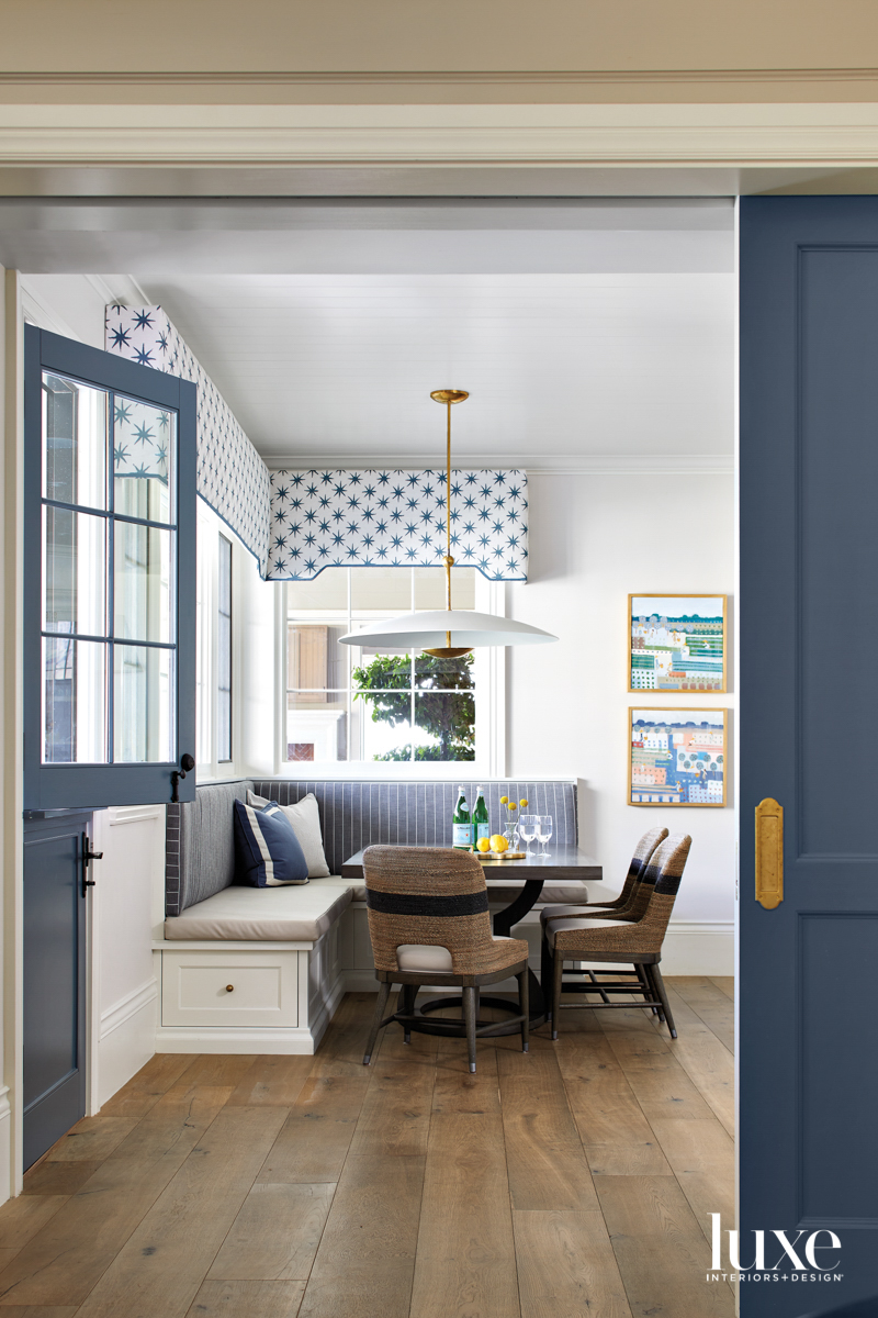 A blue-and-white striped banquette in...