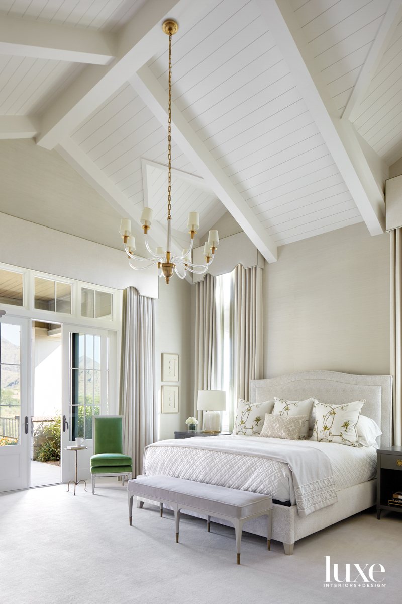 A white-and-cream bedroom with a...