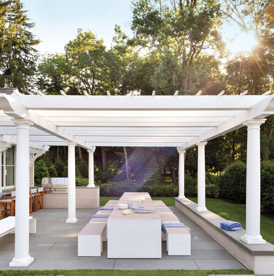 outdoor kitchen dining table under white pergola