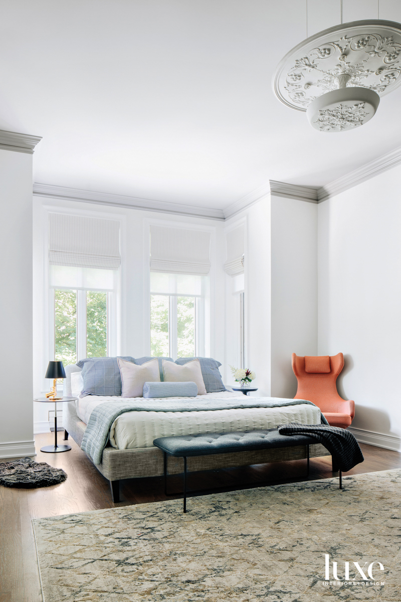 A white bedroom with blue,...