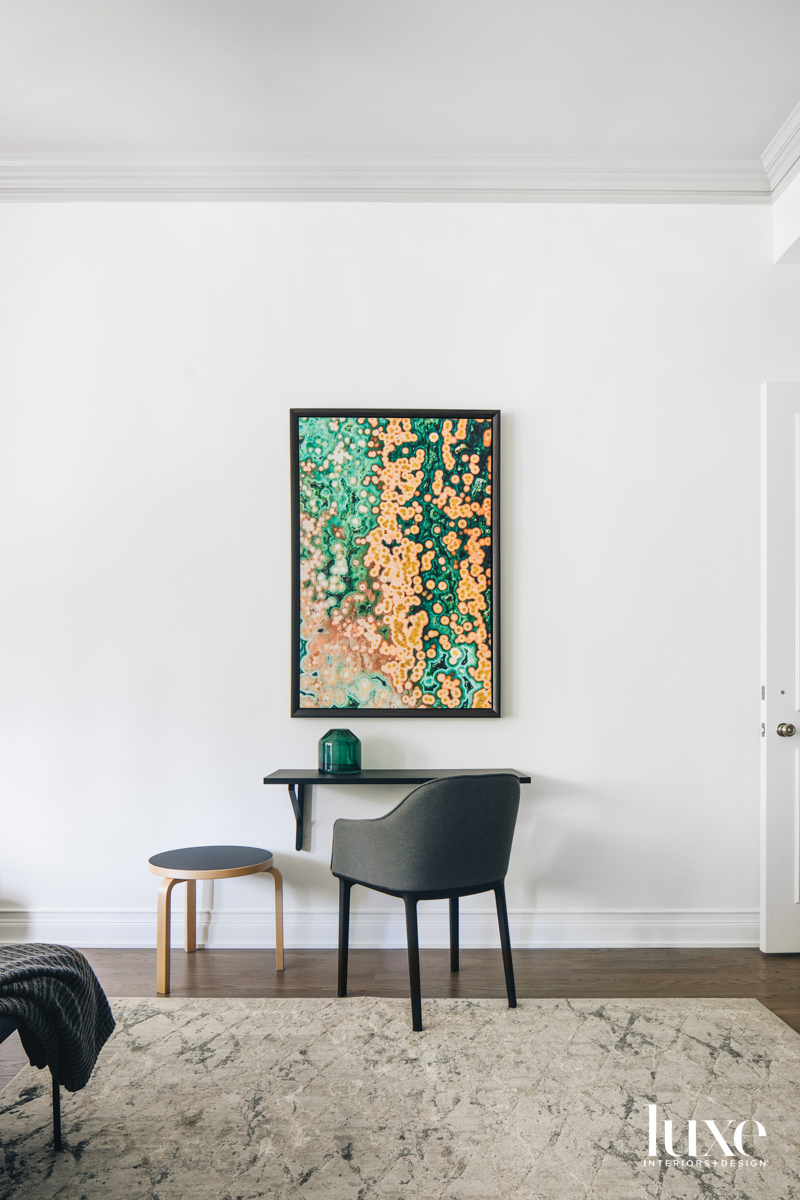 A green-and-orange contemporary artwork hangs...