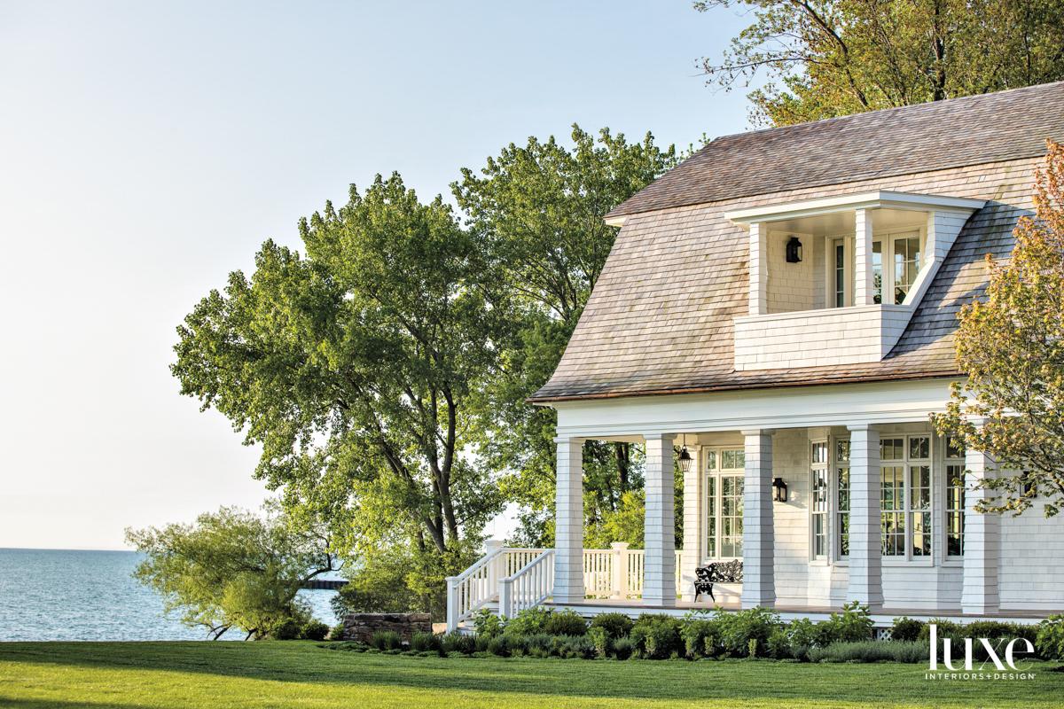 The outside of white shingle-style house on Lake Michigan.