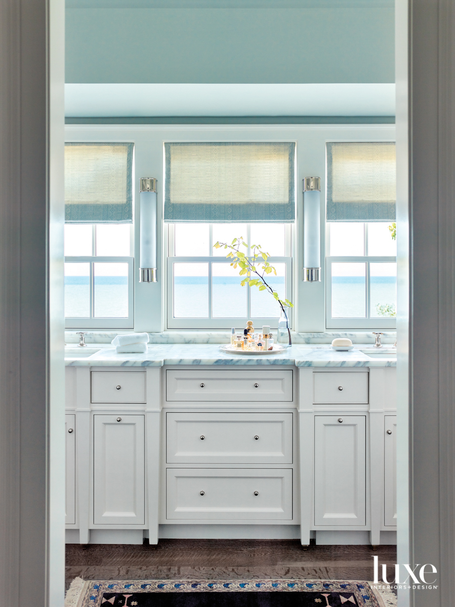 A bathroom with white cabinetry...