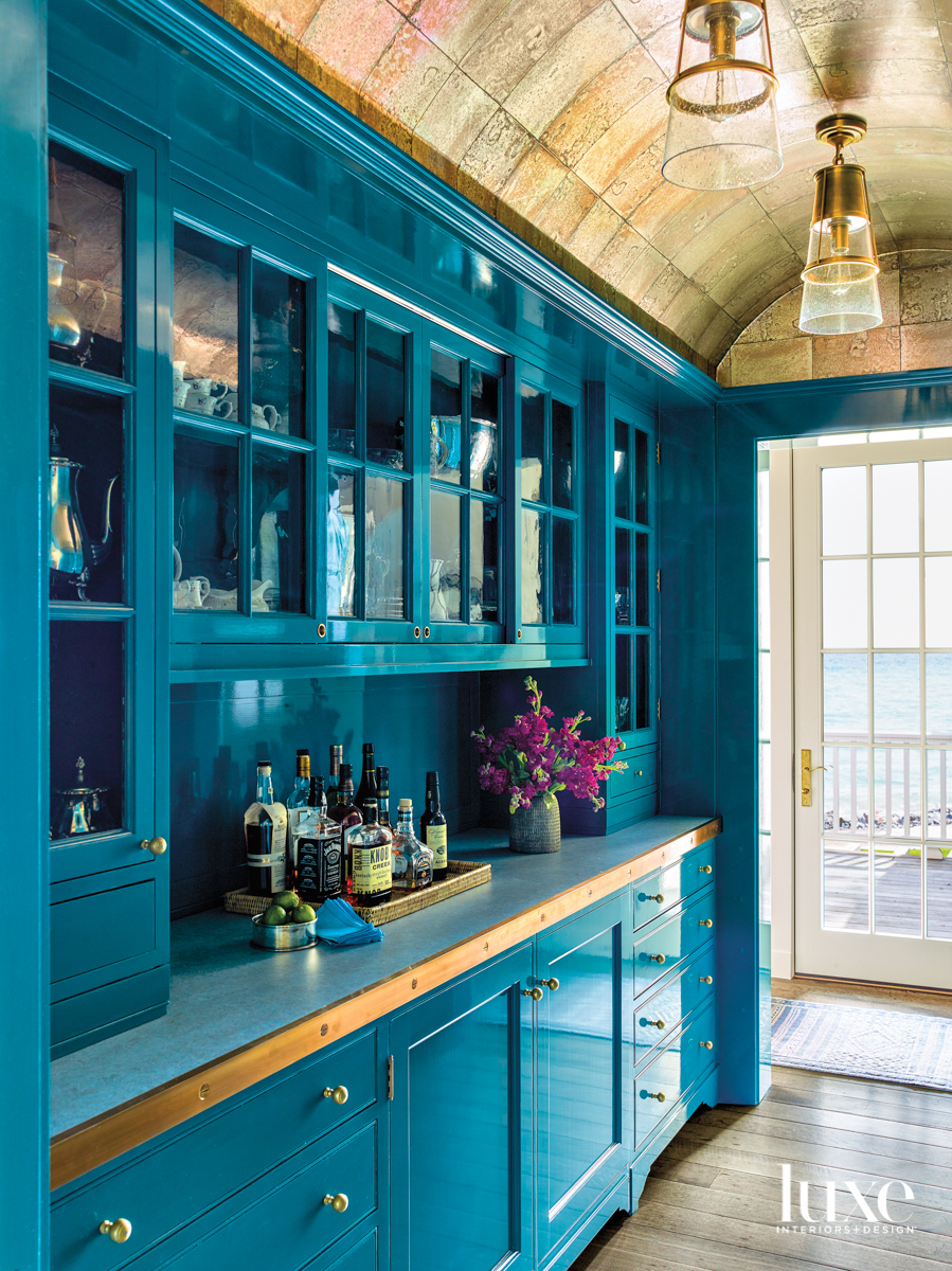 A teal cocktail pantry.