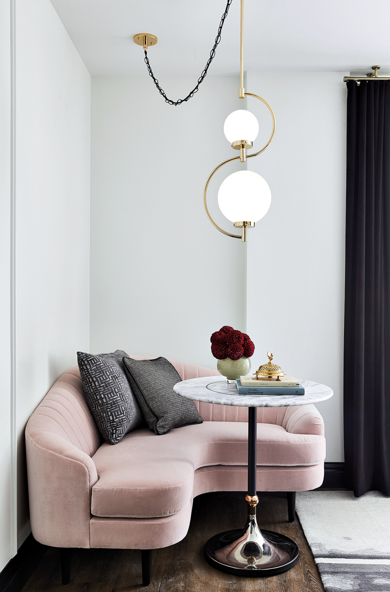 curvy pink sofa, table with flowers on it and floor lamp