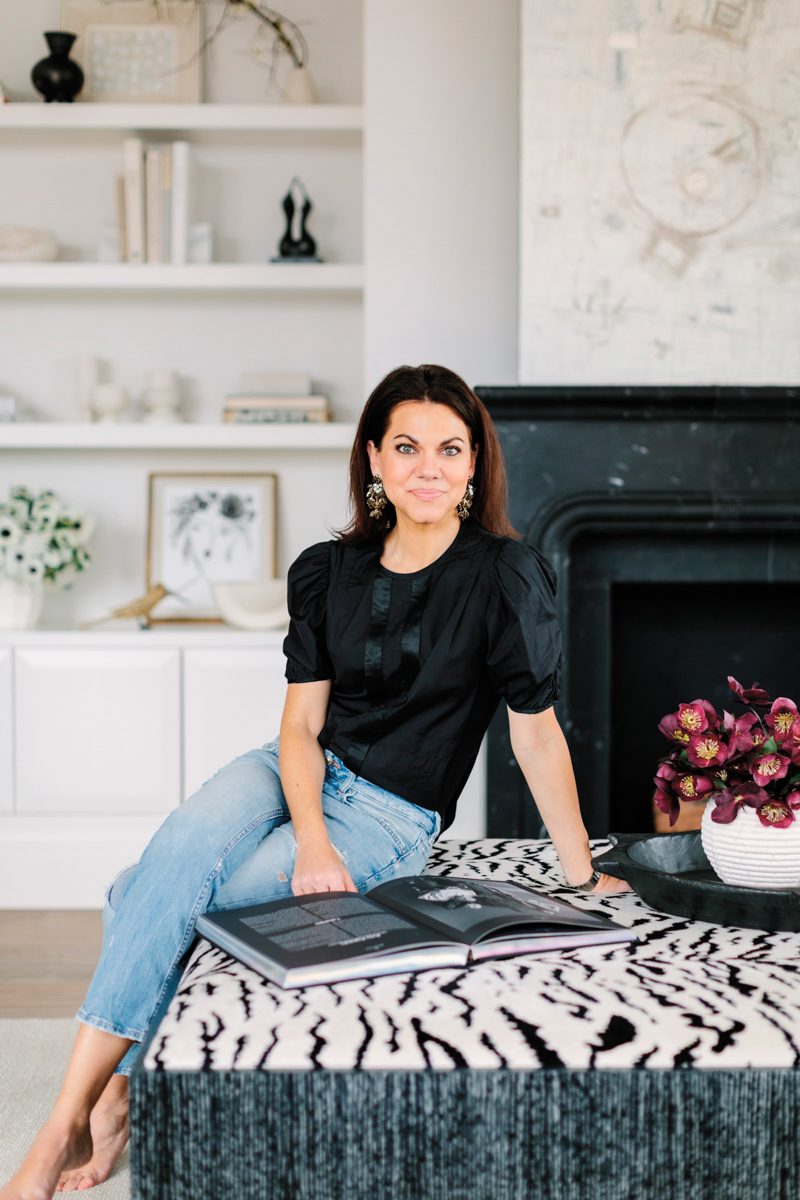 Kelly Huliman seated with book on zebra-print ottoman