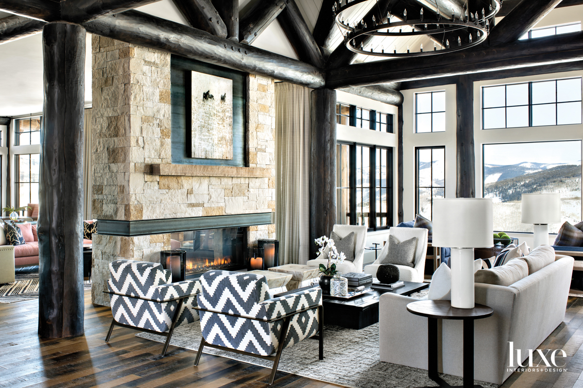 A great room has large, dark log beams; a stone fireplace; and armchairs with a geometric upholstery.
