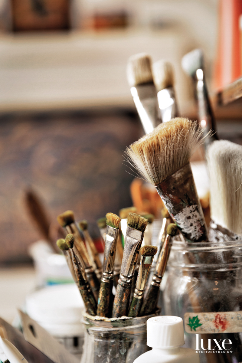 Paint brushes rest in jars.