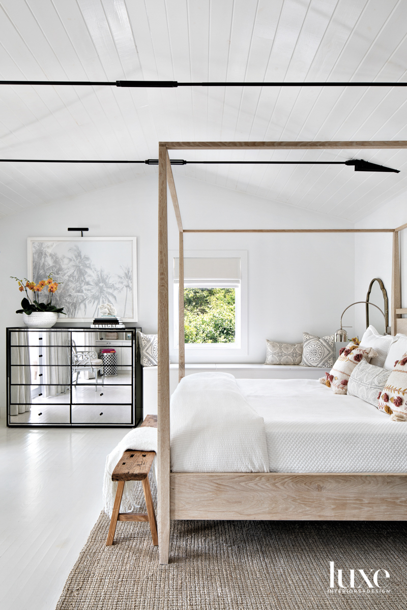 white primary bedroom with wood...