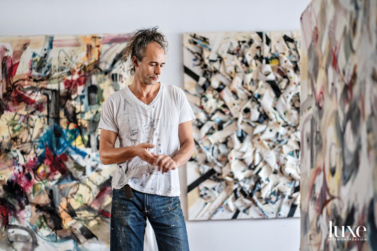 artist jordan betten in front of wall artworks